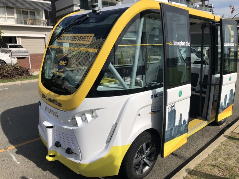 Picture of intellibus electric autonomous vehicle, white and yellow. With open doors.